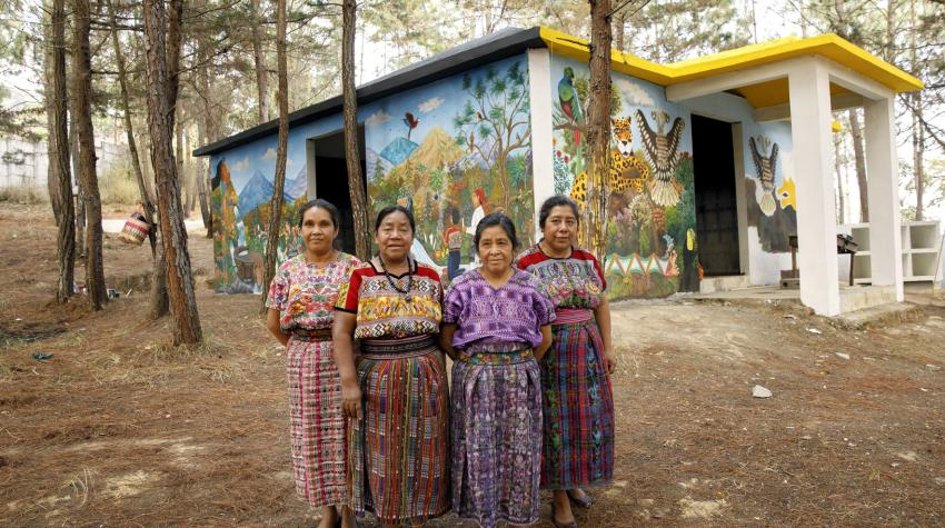 4 women artists stand in front of a hand-painted memorial for female victims of the conflict in Comalapa, Guatemala