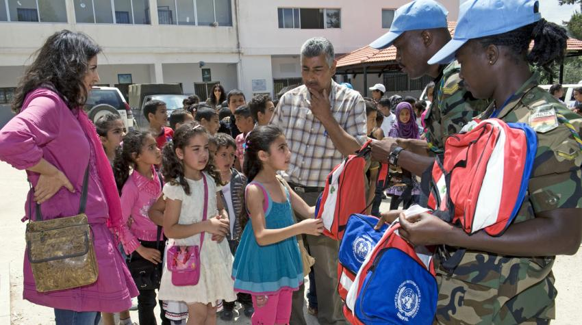 Two peacekeepers are delivering school backpacks to school children lined up.