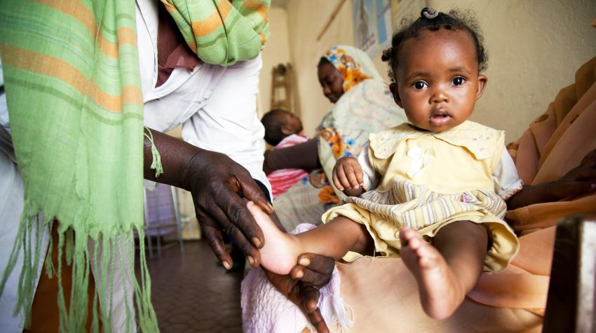 A physiotherapist massages six-month-old baby girl.