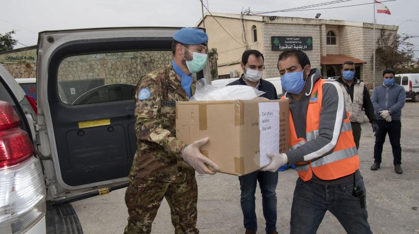 Major Stefano Parisi (left) of UNIFIL helps hand over equipment and other accessories to Naqoura Municipality in south Lebanon as part of the mission's effort to assist local communities fighting the COVID-19 pandemic. 31 March 2020. UN/Pasqual Gorriz.