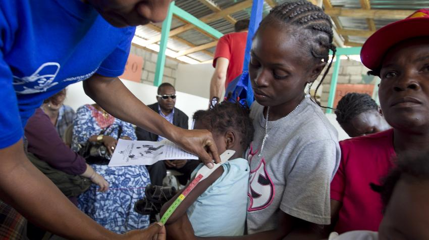 A child's arm is being measured by a staff member at a clinic in Haiti.