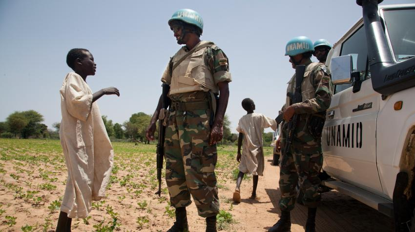 Two boys are talking to two peacekeepers standing in front of their white UNAMID vehicles in South Darfur.