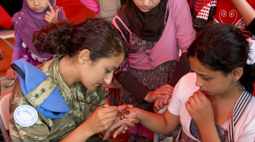 A Turkish peacekeeper paints a flower on a girl's hand at a children's fair in south Lebanon.
