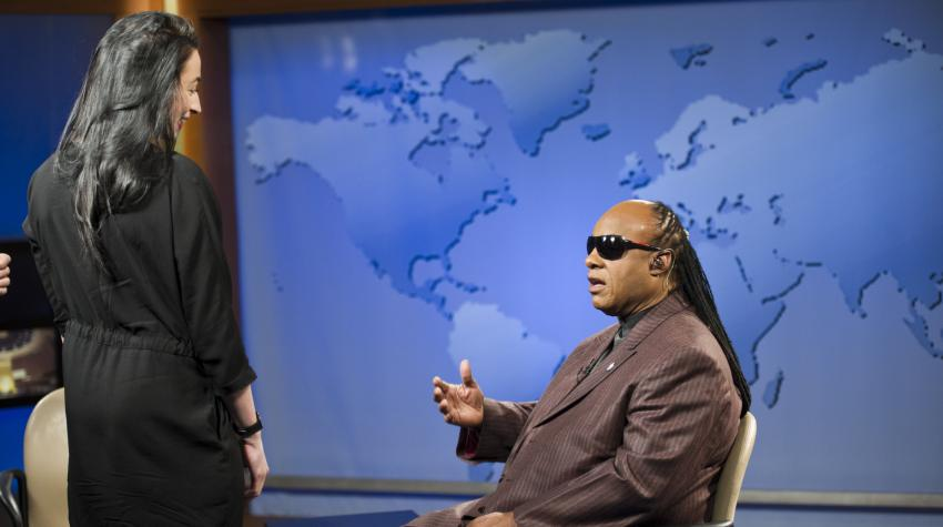 Stevie Wonder sitting on a chair with the World Map as the background.