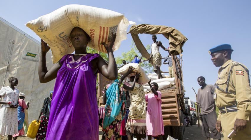 A Ugandan UN police officer based in Akobo, South Sudan, looks on as women are unloading food from a truck at a World Food Programme warehouse.