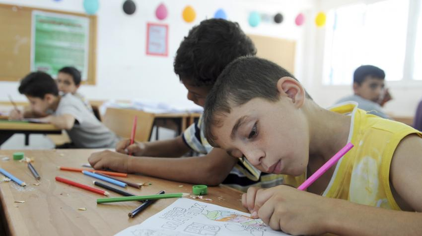 Children are drawing in a classroom as part of their summer fun weeks, organized by UNRWA.