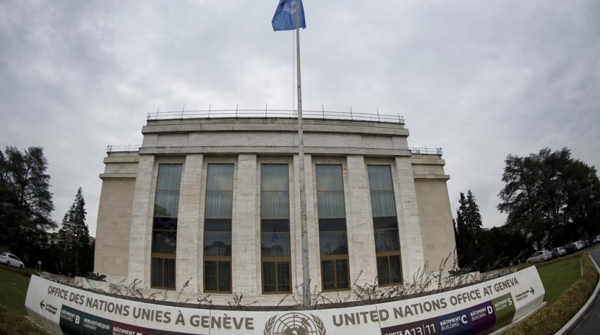A view of Palais des Nations with a banner and a UN flag in front of the building.