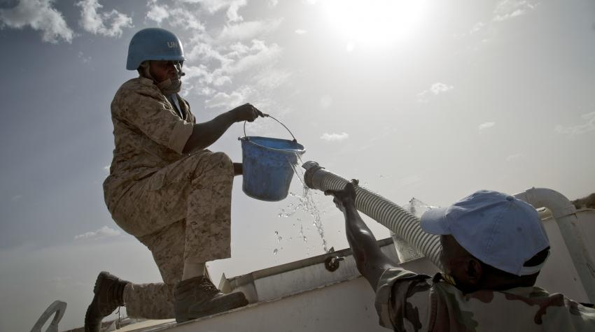 Male figure from the Ivoirian Transport Company is delivering drinkable water through a hose to a male peacekeeper holding a blue bucket.