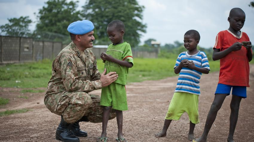 UN Military Adviser for Peacekeeping Operations smiling with three children of the town of Kaga Bandora during his visit to Central African Republic.