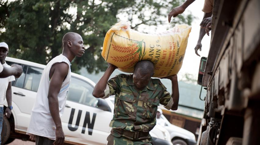 A soldier helping unload a bag of rice on his back at one of the camps for ex-combatants.