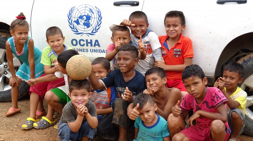 Children pose in front of an OCHA vehicle during the United Nations humanitarian needs assessment mission in Córdoba Department, northern Colombia. 2016. Photo by Felinto Córdoba/UN OCHA