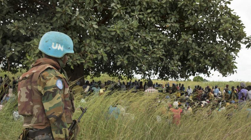 Blue-helmet peacekeeping soldier visiting a field with internally displaced people, assessing the humanitarian and security situation.