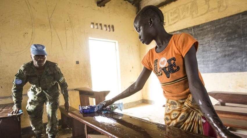 Woman and male soldier are cleaning desks of a local school in South Sudan.