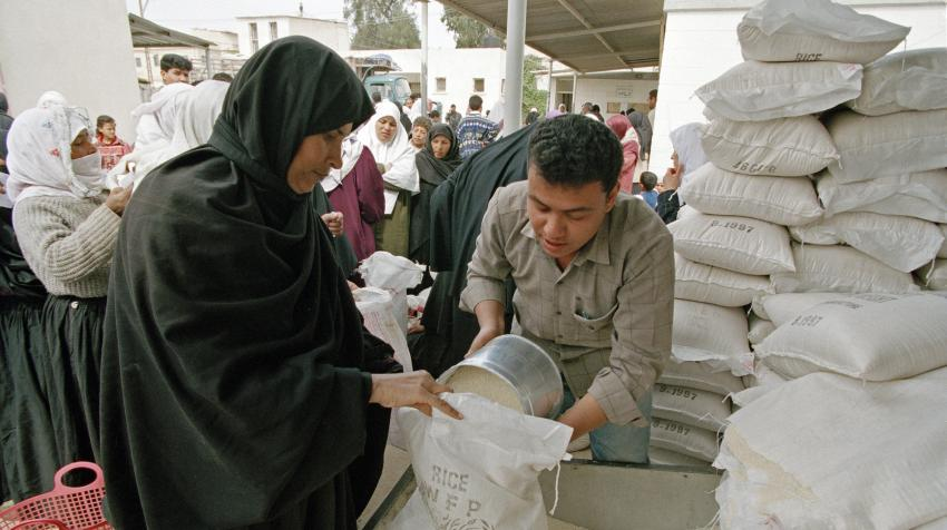 A man, in front of a huge pile of rice sacks, is distributing rice to a woman in Rafah, Gaza.