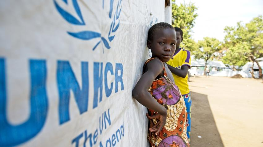 A young girl and a boy are leaning against one of the UNHCR settlement buildings in Northern Uganda.