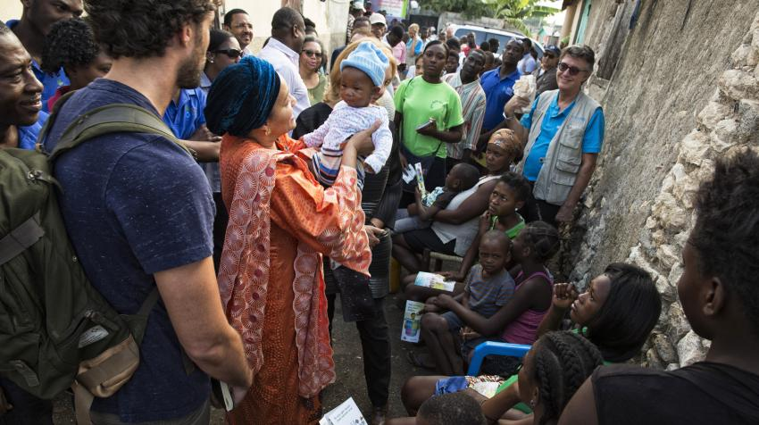 Woman, surrounded by crowd of people, is holding a baby in her arms.
