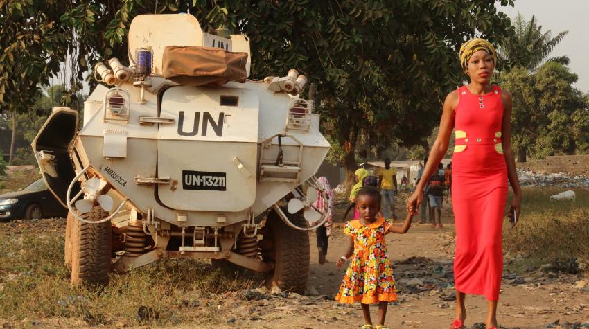 Mother and child are standing in front of a UN-engraved vehicle, celebrating a youth peace week.