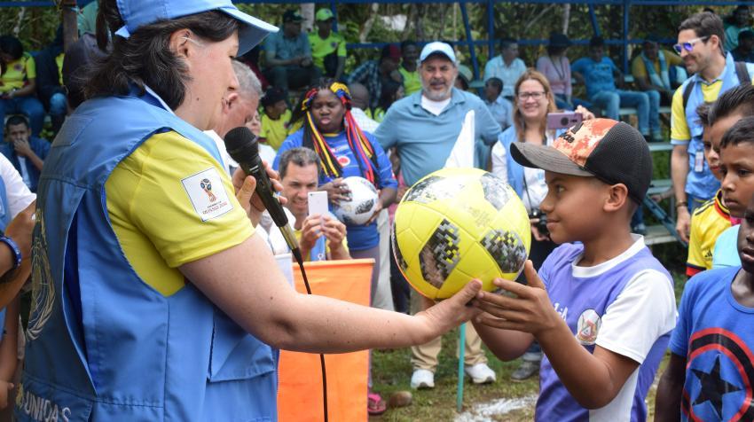A resident of Dabeiba, Colombia, is gifted a football at a match between former FARC-EP combatants and members of the Colombian Armed Forces, organized by the UN Verification Mission in Colombia. 19 June 2018. UN Photo/Jennifer Moreno Canizales.