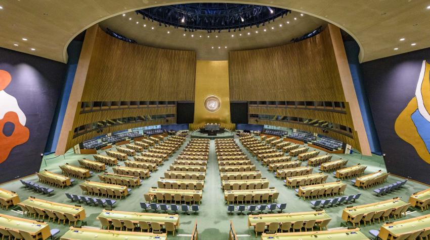 Overview of the General Assembly Hall, showing several rows of tables and seats, and murals on both sides of the back wall.