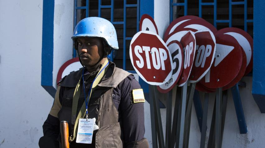 A blue helmet UN police stands guard as the delegation visits Haiti.