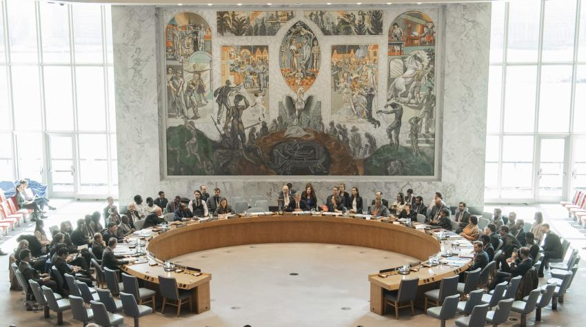 General view of the Security Council chamber with a round table for delegations and wall mural of a pheonix.