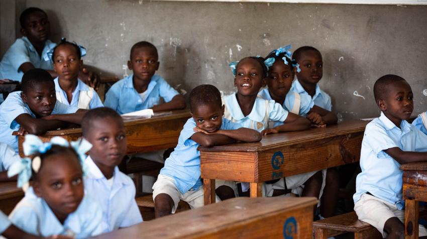 Children in school uniforms sitting on school desks.