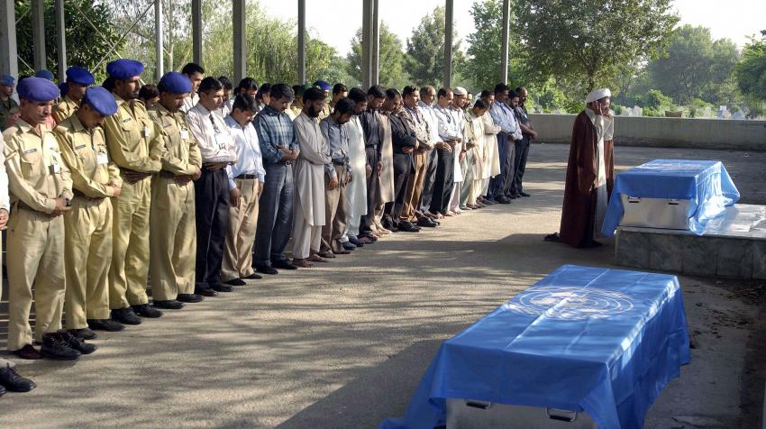 Military staff and other mourners are commemorating a UN staff and his son, who were killed during the Pakistan Quake.