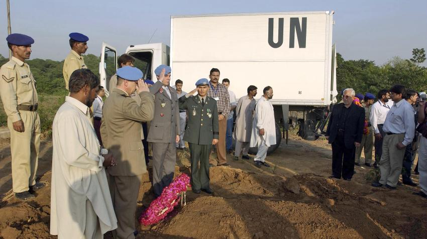 Military staff and other mourners are commemorating at the burial site of the UN staff and his son who were killed during the Pakistan Quake.