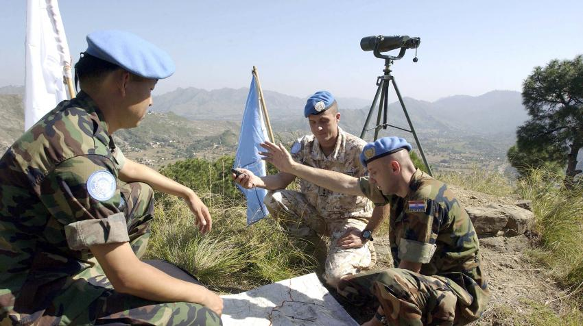 Three peacekeepers are going over their plans near the UN field station in Pakistan