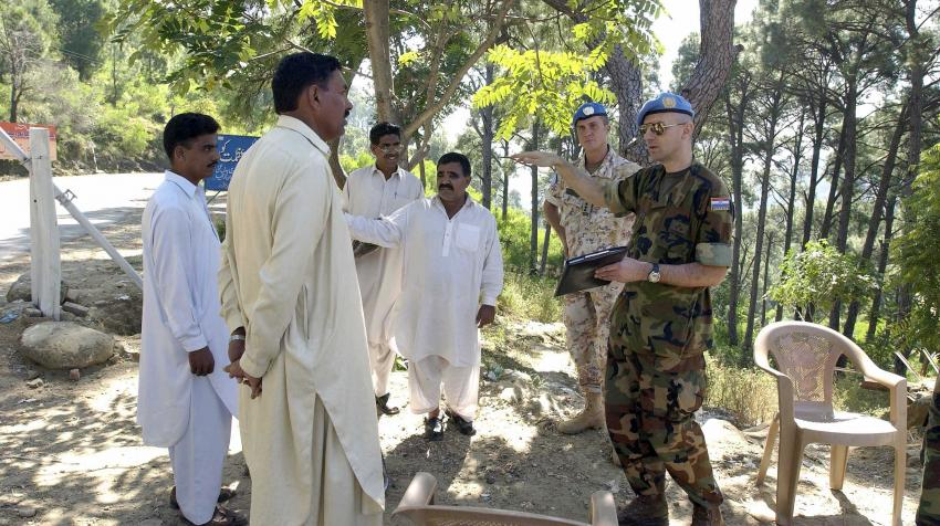 Two peacekeepers are speaking with local Pakistani men.