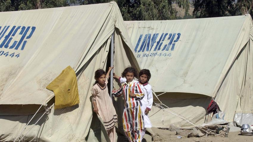 Three girls are in front of a tent set up by the office of the United Nations High Commissioner for Refugees.