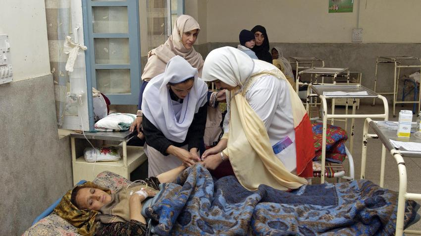 A woman who had given birth two hours earlier and is a victim of the earthquake that hit Pakistan, is being treated in a hospital by several other women.
