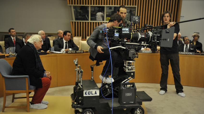 Picture of filming crew in the Security Council chamber with the director behind the cameraman.