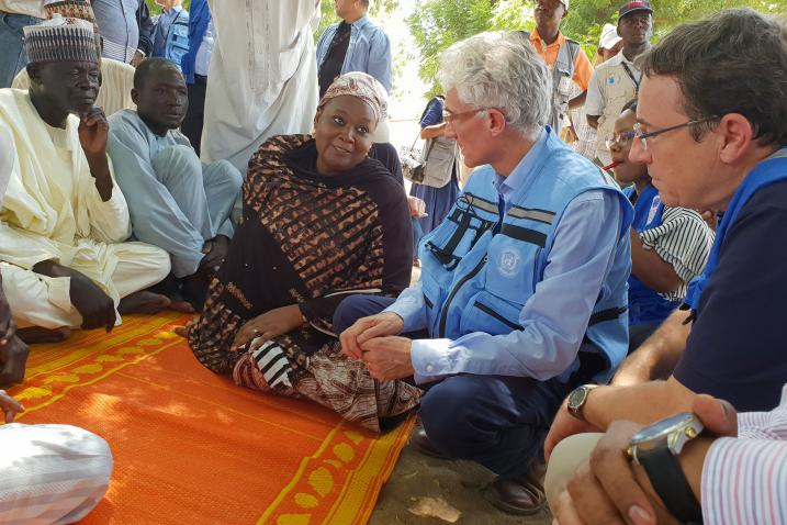 Mark Lowcock and UNDP Administrator Achim Steiner with the head of the Nigeria State Emergency Management Agency, are pictured seated on the ground and speaking with a group of farmers from the border town of Banki.