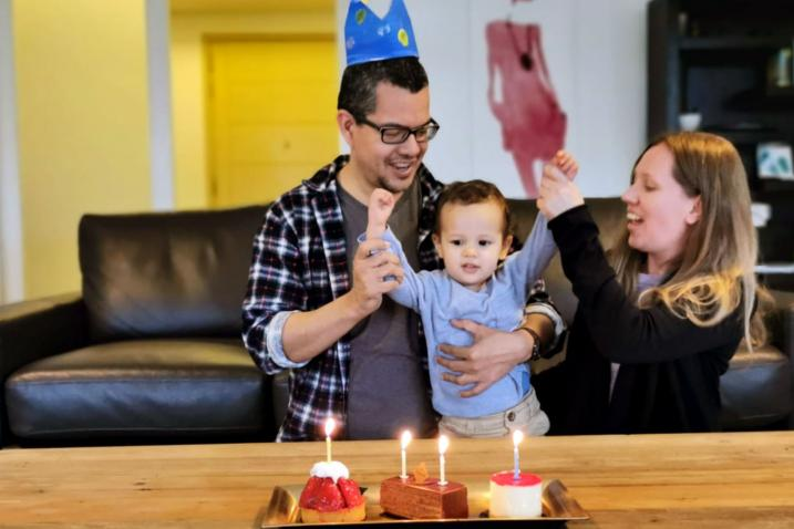 Sarah with husband and Issac celebrating the child's birthday with a cake and candles.