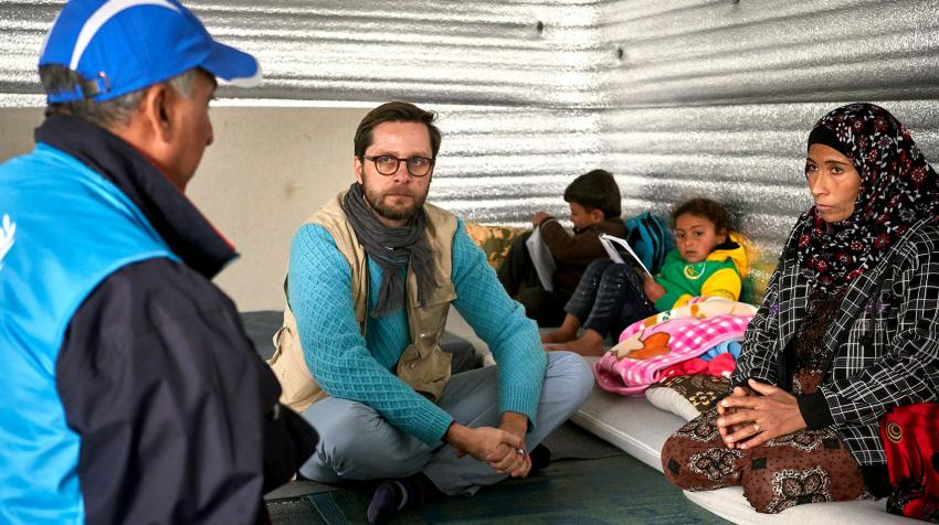Three adults and two children are sitting on the floor in a refugee makeshift home. The adults are talking and look concerned.