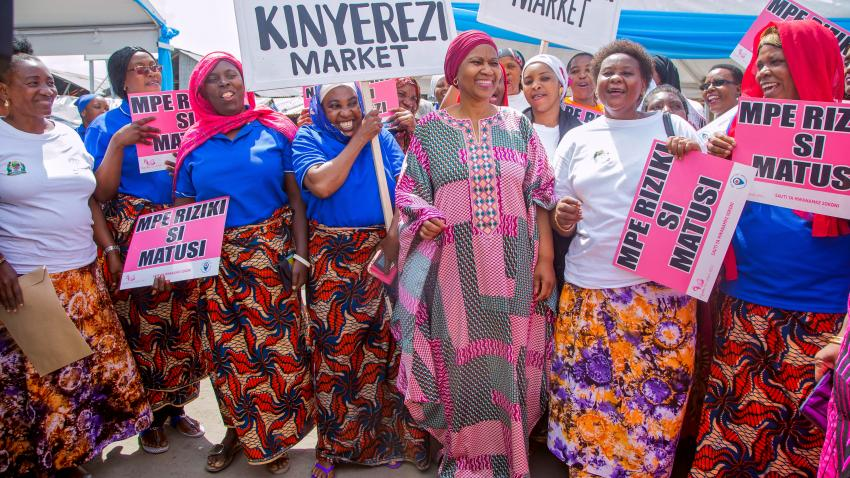 Phumzile dressed in bright traditional African clothes is surrounded by African women holding up signs.