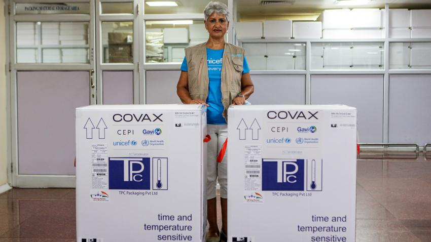 Yasmin is pictured inside a vaccine manufacturing plant. She stands between 2 large COVID vaccine containers.