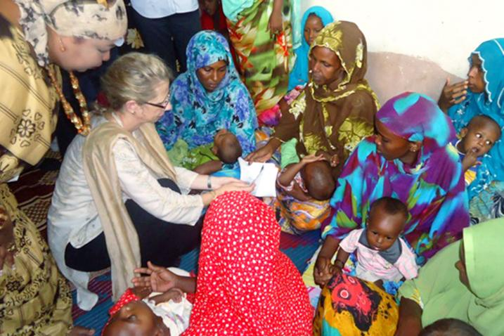 Inger Andersen is surrounded by women and children in a maternal health facility.