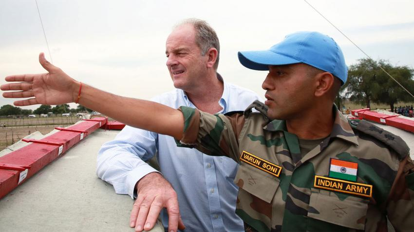 An officer from the Indian army is on a rooftop with David Shearer. The officer is pointing left and both men are looking in that direction.