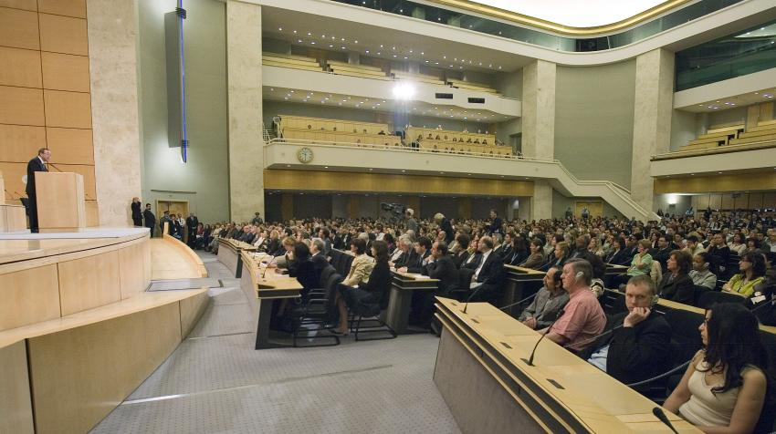 Floor level view of man speaking at podium and audience listening below, behind having 2 more floors for seats.