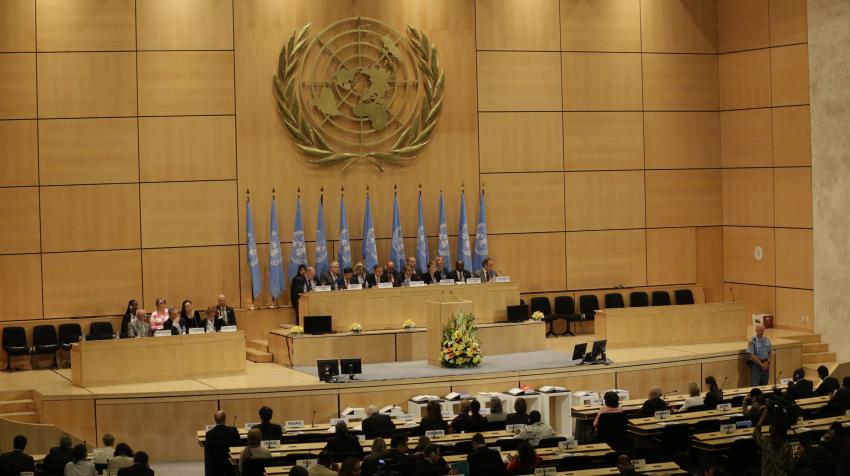 Front view of the Assembly Hall with several rows of seats and a stage with elevated tables and series of UN flags under UN emblem.