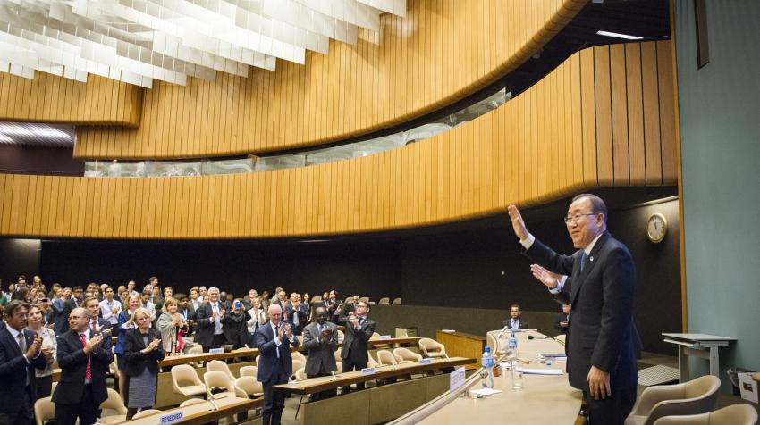 Former Secretary-General Ban Ki-moon waving in front of the Hall while a standing audience applauds. The Hall's walls are partially composed of wood with a ceiling composed of rows of hanging white tiles.