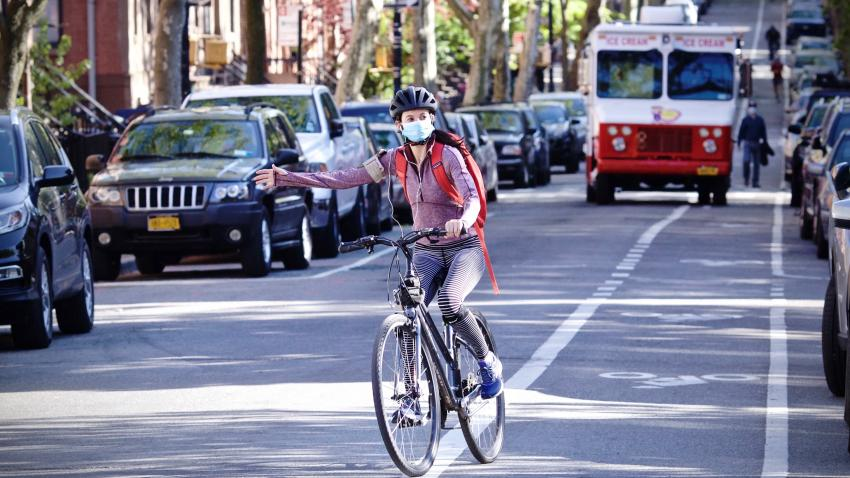 A bicyclist wearing a mask signals while making a turn.