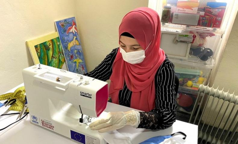 woman with face mask and gloves at sewing machine