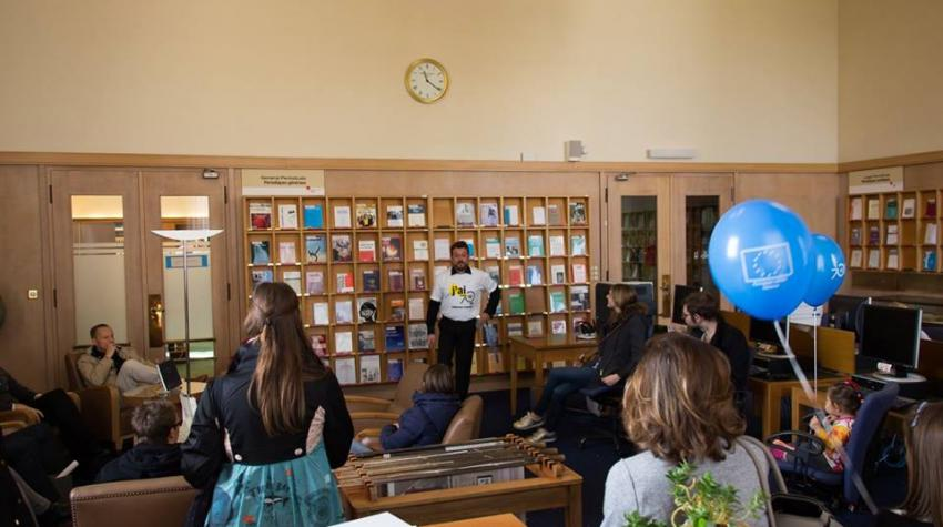 View of library wall full of books and people seated, listening to a speaker.