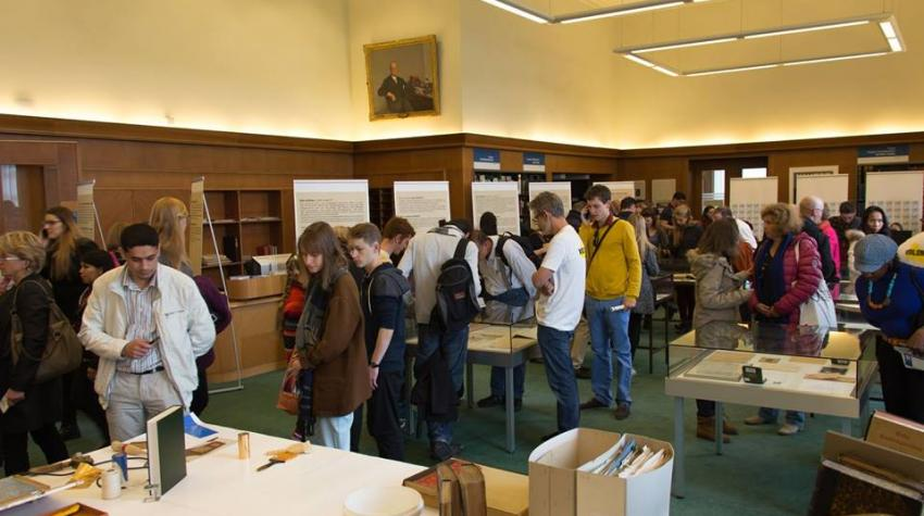 View of green-carpeted open space of the library with tables and posters, and people walking around the room.