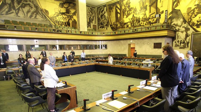 View of green-carpeted Council chamber from floor including standing individuals and artwork on second level