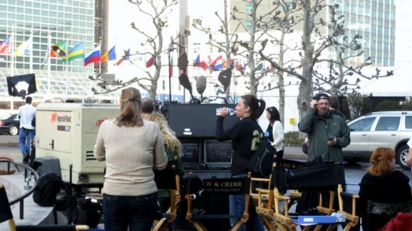 Law and Order staff are standing outside the UN headquarters building with filming equipment.