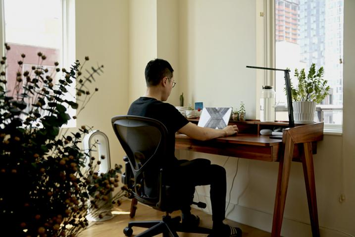 Man sitting at a desk with a laptop.